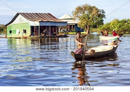 Tonle Sap lake, Cambodia - January 04, 2017: View of an unidentified man rowing in his boat. Tonle Sap refers to a freshwater lake that form the central part of cambodian hydrological system