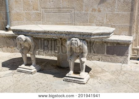 PERAST, MONTENEGRO - AUGUST 04, 2017:Stone table with male figures near the church on the island of Gospa od Skrpela in the Boko-Kotorsky Gulf. Montenegro.