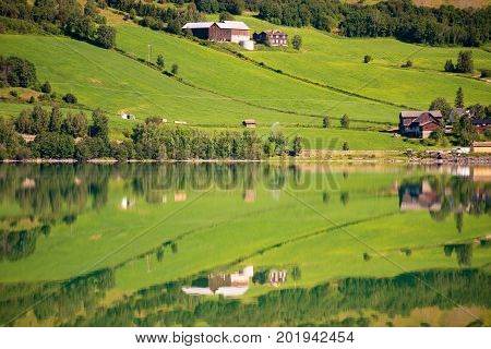 Norway country houses. Lake and meadows. Reflection in water. Nordic Scandinavia Europe travel