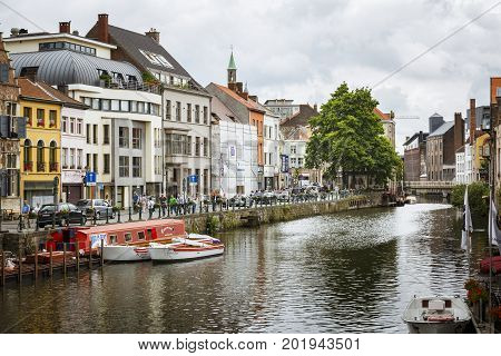 GHENT BELGIUM - JUNE 22 2016: Horizontal picture of one of Ghent's canal with boats houses sidewalk with people passing with a bridge in the end with a tree in a cloudy day in Ghent.