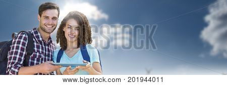 Digital composite of Students holding tablet in front of sky