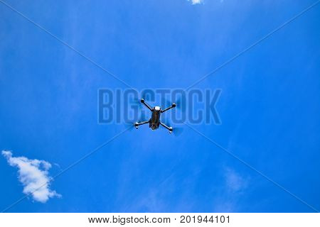 A small gray quadrocopter against the blue sky.