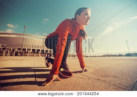 Fitness athlete on starting near stadium track preparing for a sprint. Fitness, healthy lifestyle concept