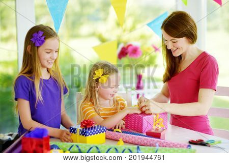 Two Cute Sisters And Their Young Mother Wrapping Gifts In Colorful Wrapping Paper
