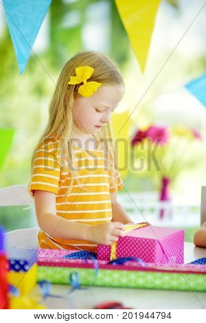 Cute Preschooler Girl Wrapping Gifts In Colorful Wrapping Paper.