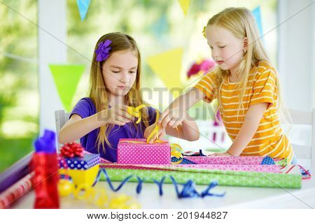 Two Cute Sisters Wrapping Gifts In Colorful Wrapping Paper