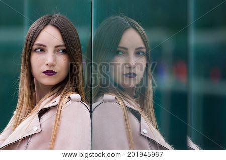 Reflection of beautiful informal fashionable girl in modern glass building