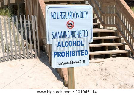 Two signs at the beach that read no lifeguards on duty and alcohol prohibited.