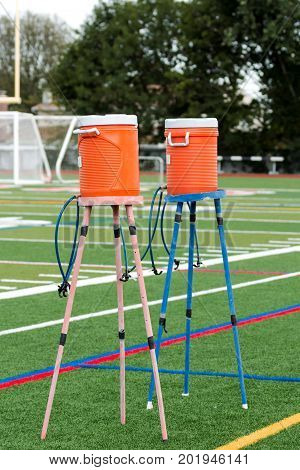 Two water coolers on stands with multiple spouts to hydrate athletes practicing on a green turf field.