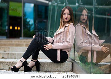 Portrait of beautiful informal fashionable girl on modern building background