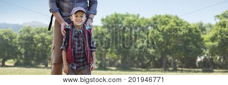 Digital composite of Father hands on son's shoulders against blurry trees