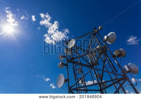 Telecommunication tower with microwave radio antennas and satellite dishes with shadows on the roof against blue sky and sun