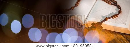 Digital composite of Rosary on bible and brown blue bokeh transition