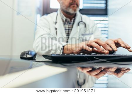 Closeup of hands of male doctor typing on computer keyboard. Medical professional using computer keyboard in clinic.