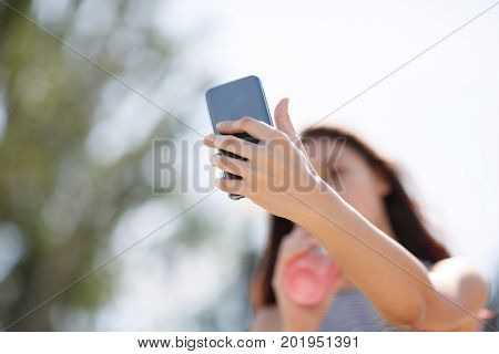 A close-up picture of a charming young lady in striped T-shirt taking a selfie with a refreshing pink beverage in a plastic cup on a natural blurred background. A fashion girl makes a self-portrait.