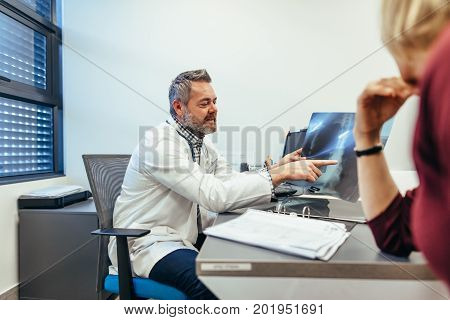 Medical specialist discussing medical scan result with female patient in his clinic. Doctor showing x-rays to patient in medical office.