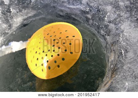 Closeup of an Ice Scoop Skimmer in a Fishing Hole