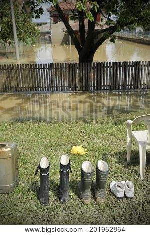 Concept photo of flooding. Waterproof rubber boots