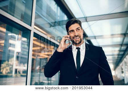 Businessman on business trip talking on his mobile phone at airport. Caucasian businessman using mobile phone and smiling.