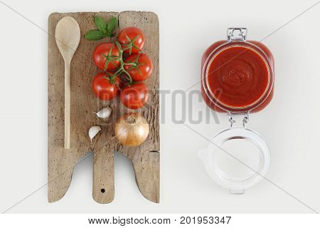 Concept of cooking with wooden cutting board tomatos onion basil garlic and tomatoes sauce in glass jar isolated on kitchen white worktop copy space top view