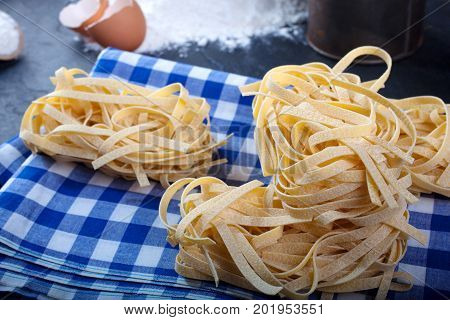 Italian homemade pasta called fettuccine on blue and white chequered dishcloth