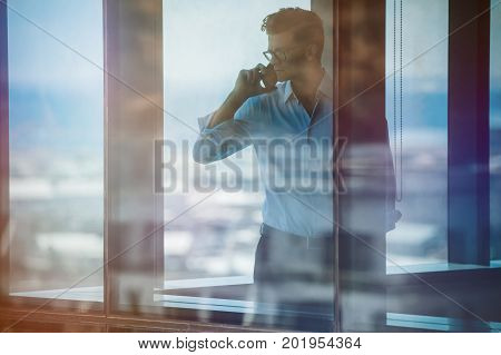 Mature business man standing inside office building and using cell phone. Man standing by window and talking on mobile phone.