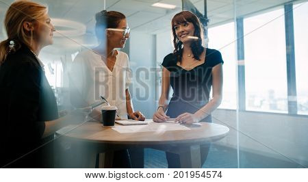 Three female executives standing and discussing around a table. Corporate professional having an informal meeting in modern office.