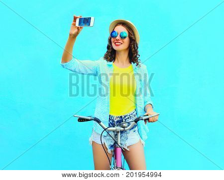 Summer Young Woman Take Self Portrait On The Smartphone With Retro Bicycle On A Colorful Blue Backgr