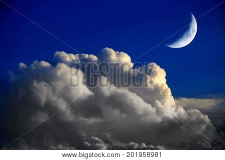 Stark Blue Sky with thunder clouds and crescent moon