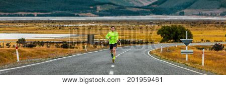 Runner man running on road in autumn banner countryside landscape in cold weather fall season. Male athlete runner training cardio on morning dawn exercising in nature background.
