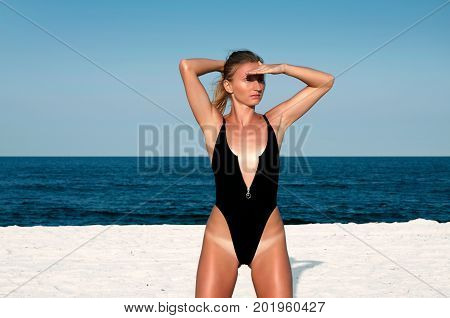 Beautiful Woman In Black Swimsuit On The Beach.