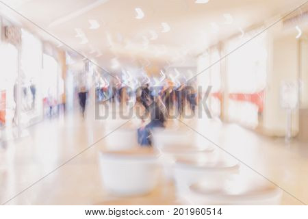 Abstract background of people walking young people in the shopping center back to us. Intentional motion blur. Concept of shopping, walking, lifestyle, modern city. Abstract defocused motion blurred people