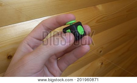 Male Hand Uses A Black And Green Fidget Cube-antistress