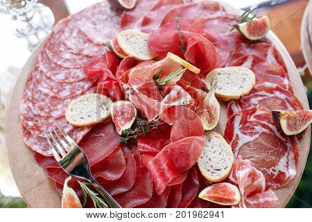 Italian antipasti and appetizers. board with slices prosciutto, salami, dried pork, salami ham with herbs. bread croutons. top view