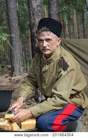 Reconstruction of the events of World war II, Russia, Dimitrovgrad, 26 Aug 2017. Portrait of a red army soldier, cut the bread for dinner.