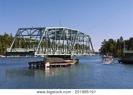 Rare swing drawbridge provides opening for lobster boat to pass by in Boothbay region in maine.