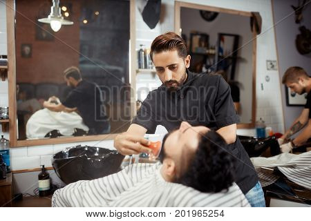 View of young hairstylist in black combing out, caring face and cutting bread for brunet client at barbershop. Brunet man visiting professional hairdresser at modern barber shop.