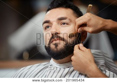 Close up of smiling man who visiting barbershop, sitting at chair, when barber doing correction of bread and cutting hair. Brunet man who caring about himself.