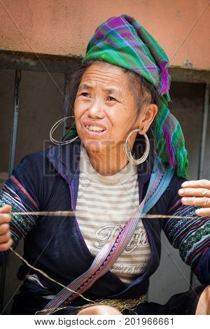 SA PA, VIETNAM - AUGUST 2017: Portrait of black hmong ethnic minority woman selling goods at the market in Sa Pa town, the high mountains, Lao Cai province, Vietnam