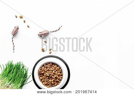 plastic bowl full and overflowing with dry pet - cat food bits and mouse toy on white table background top view mock-up