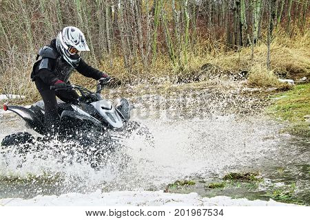 Child quading through large water puddle in spring.