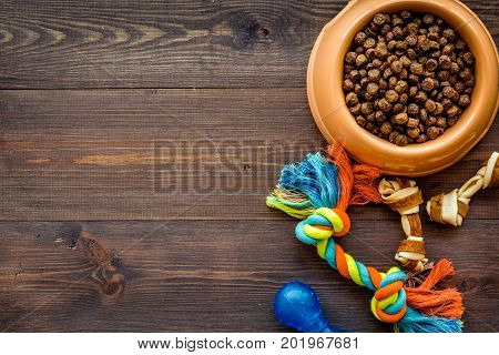 large plastic bowl of pet - dog food with toys on wooden table background top view mockup