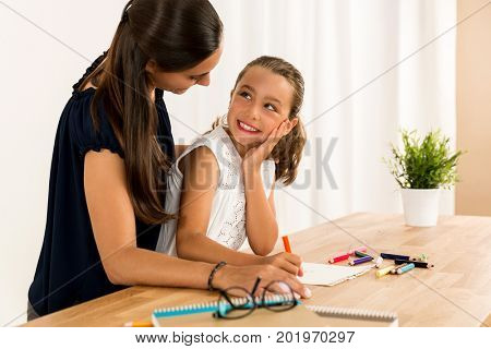 Young mother helping her daughter with homework at home