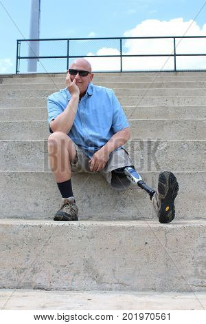 Seated amputee man with prosthetic leg extended