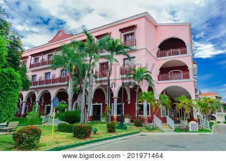 Cayo Coco island, Cuba, Colonial hotel, July 16, 2017, gorgeous amazing view of Colonial hotel grounds, beautiful inviting retro stylish main building in tropical garden on blue sky background