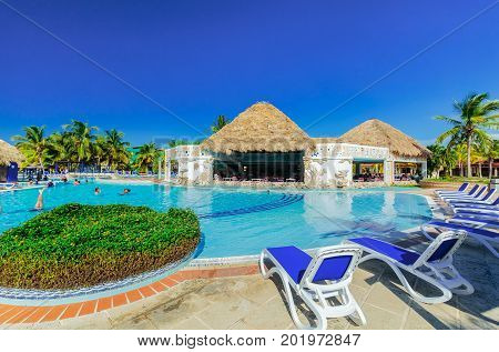 Cayo Coco island, Cuba, Iberostar Mojito resort, July 17, 2017, gorgeous amazing view of hotel grounds with nice inviting swimming pool and people relaxing in water in tropical garden on sunny day