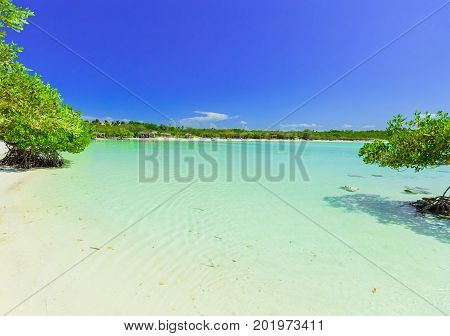 nice beautiful, inviting view of lagoon with turquoise tranquil ocean with tropical beach in background at Cayo Coco island, Cuba on sunny day