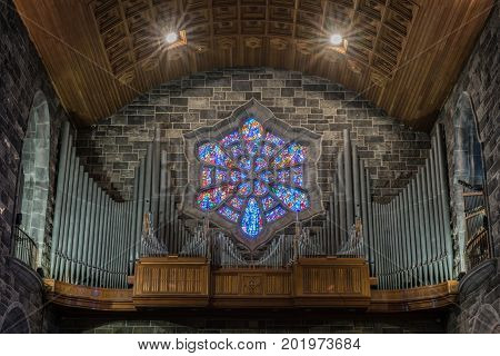 Galway Ireland - August 5 2017: Closeup of gray pipes and brown wood form the Organ gallery of the Cathedral. Backdrop of hexagon stained window and wooden vaulted ceiling above.