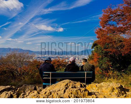 Old group of men enjoying the beautiful landscape from hanami park during autumn season in Kyoto, Japan.