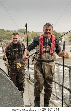 Galway Ireland - August 5 2017: Closeup of two laughing fishermen with gear and waders fleeing heavy rain over Corrib River control dam. Gray sky and faint green of trees in background.